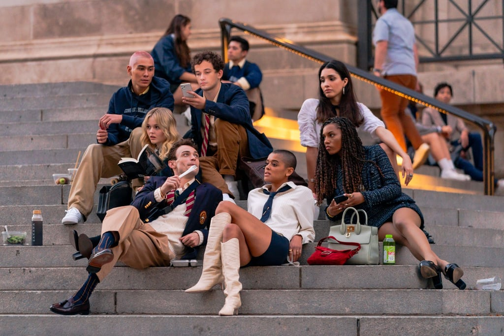 A new crew of Upper East Siders are here, and they're taking their rightful spots on the iconic Met steps. After production was put on hold due to the coronavirus pandemic, HBO Max's Gossip Girl reboot started filming this week in NYC — and thanks to behind-the-scenes shots of the cast on set, we caught a glimpse of the next generation of Manhattan's elite and their perfectly preppy outfits. The new cast, which includes actors Jordan Alexander, Emily Alyn Lind, Whitney Peak, Thomas Doherty, and Zion Moreno, were photographed filming on Nov. 10 on the steps of the Metropolitan Museum of Art, where original Gossip Girl characters Blair Waldorf, Serena van der Woodsen, and their minions often spent their days. Judging by the first-look photos, it appears the wardrobe of Gossip Girl 2.0 is heavily inspired by the original, but with a 2020 update. This comes as no surprise, as costume designer Eric Daman, who was the creative genius behind the original series, has also returned for the spinoff. While there may be no headbands in sight, the Constance Billard and St. Jude's uniforms — and the loose ties, smart blazers, and tweed — are all too familiar for OG fans. On another day of filming, on Nov. 8, cast members Alexander, Moreno, and Savannah Lee Smith were seen in glam evening gowns that certainly remind us of the dramatic galas and epic parties from the CW show.  While it's been over a decade since Gossip Girl first aired, Blair and Serena's style continues to influence our fashion choices today, so it's safe to say we expect some serious inspiration from the reboot as well. Take a closer look at the new crop of Upper East Siders' chic looks ahead.