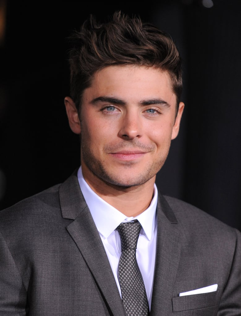 Zac Efron in a grey suit.