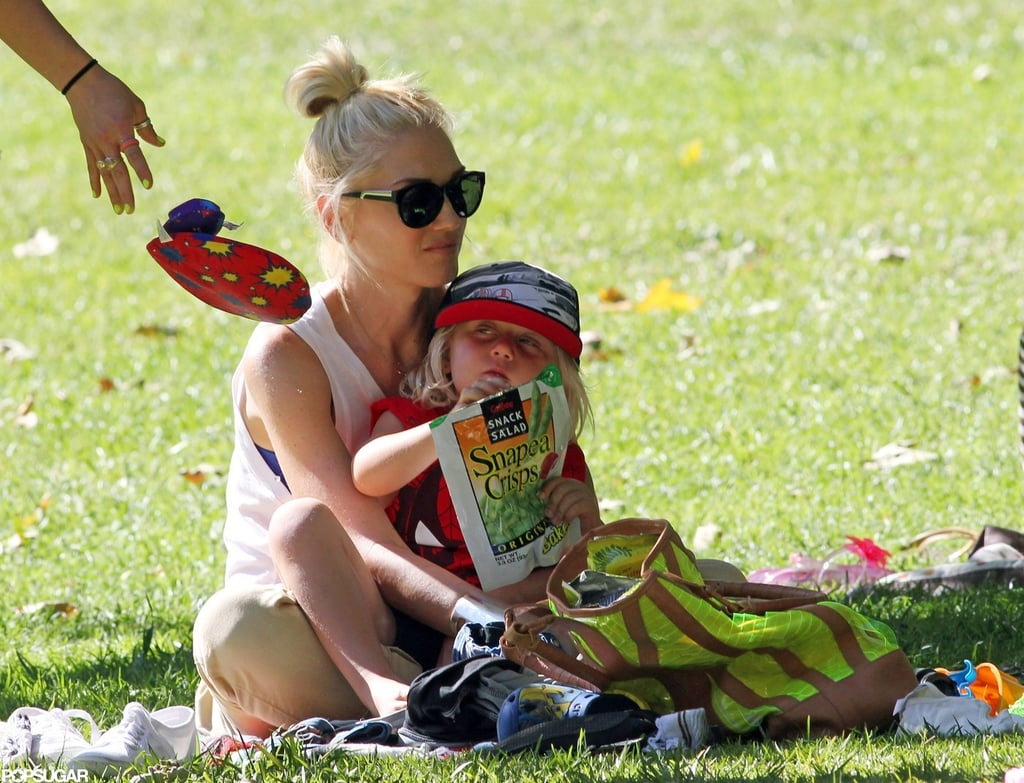 Gwen Stefani held Zuma in her lap while he snacked.