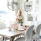 Our dining area consists of a large restored wood table. It's both manly and feminine all at the same time. I especially fell in love with the whimsical legs finished off with gorgeous white Louis leather chairs. Although, I must say the main focal points are the Victorian pendants above the table. Again, both manly and feminine all in one! They absolutely make the space.