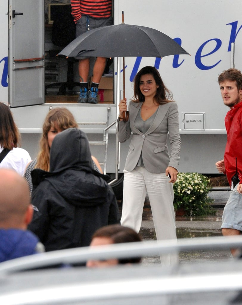 Penelope Cruz walked through set with an umbrella in her hand.