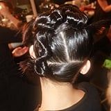 "The second style was a twisted and twirled updo with straight, sharp partings. If you want to get a perfect part every time, remember Pecis's tip: ""Put a little water on the hair, and brush through with the teeth. Watch where the hair starts to split, and from there use the tail comb to help refine it."""