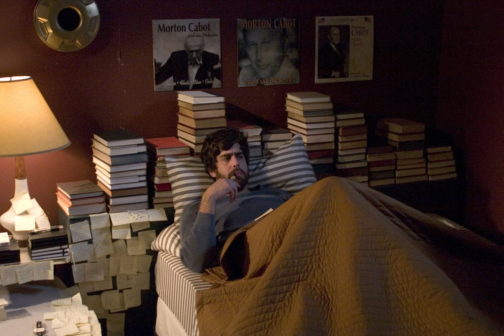 Striped bedding in Goldberg's character's bedroom plays well with his linear stacks of books.