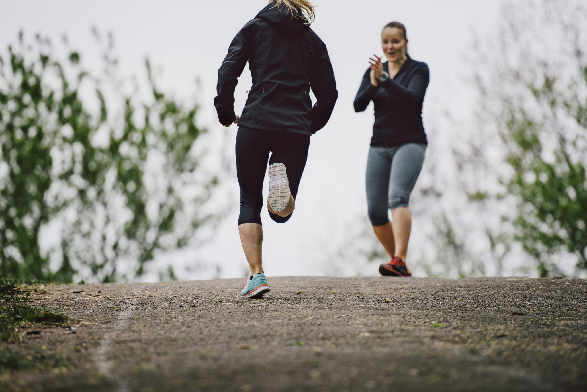 Women running together uphill in a park