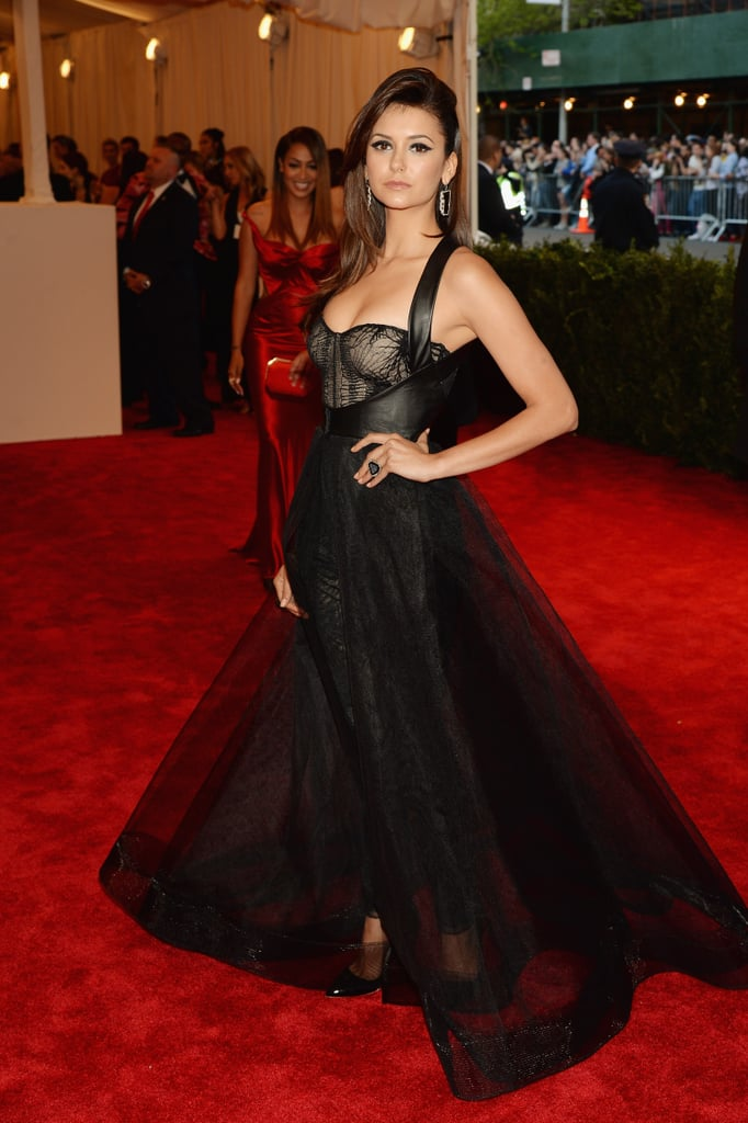 Nina Dobrev donned a Monique Lhuillier gown to hit the red carpet as a guest of the designer at tonight's Costume Institute Benefit at the Metropolitan Museum of Art. Nina also walked the carpet at last year's event, though she had a different date in boyfriend Ian Somerhalder for the 2012 occasion. She's been making waves in the fashion world, so it's no surprise that Nina is joining in the festivities to celebrate the opening of the museum's new exhibit, Punk: Chaos to Couture. Nina's gown played on the evening's theme with its leather harness and corset details. Nina will was in good company since she met up with her close friend Julianne Hough on the red carpet. Julianne and Nina are fresh off a beach getaway to Miami, where they lounged in bikinis together two weeks ago. What do you think of their gowns tonight? Weigh in on their choices and many more in our fashion and beauty polls!