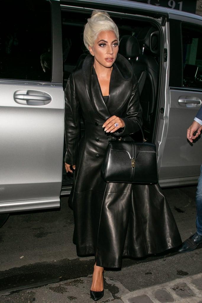 مرتديةً معطفاً جلديّاً من تصميم عليّة مع حقيبة يد من علامة سيلين.