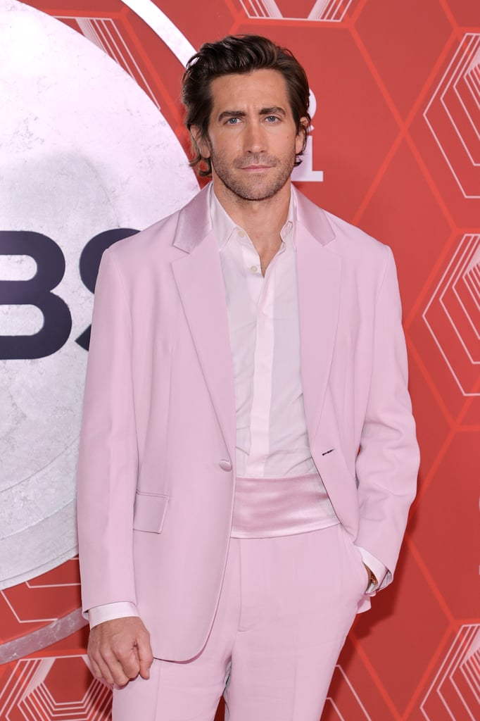 Jake Gyllenhaal sees your black-and-white tuxedo and raises you a perfectly pastel colour palette. On Sept. 26, the handsome actor posed for photos at the 2021 Tony Awards in New York wearing a pale pink custom Prada tuxedo. He was styled by Michael Fisher, who shared photos on his Instagram Stories of the look being designed, and it's clear this was perfectly made for Jake. He was nominated for his performance in Sea Wall/A Life, and lit up the carpet with his fresh take on a tuxedo.  Despite ditching a traditional bow tie, Jake looked sharp as ever with a silk collar and a matching silk cummerbund around his waist to complete the all-pink look. Jake presented an award during the show with his Sunday In The Park With George costar Annaleigh Ashford. Check out the dapper photos of Jake in his custom pink Prada tuxedo at the Tonys.      Related:                                                                                                           Get Ready to Serve Looks This Fall With These Exciting Tips on Colourful Layering