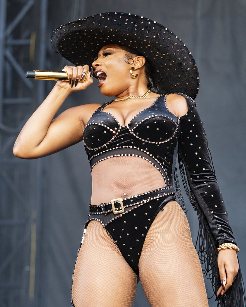 """Megan Thee Stallion may not have a horse, but she's riding into October in style. During a performance at Austin City Limits Music Festival on Oct. 8, Megan took the stage in an asymmetrical rhinestone bodysuit that puts a 2021 twist on classic cowboy fashion. On her right, the plunging one-piece included a strap down her thigh to hold her single chap in place, and on her left, the outfit extended into a single fringe-covered sleeve that flowed behind her like a cape in the wind. The velvet and mesh bodysuit even included a built-in belt buckle and came with a matching, extra wide-brimmed hat that reflected all the shimmer and shine coming off the """"WAP"""" singer.   Megan completed the look with black combat boots, gold jewelry from Kendra Scott and Past Midnight, and an iridescent manicure. Covered in rhinestones and gold stars, the thong bodysuit was clearly Megan's way of telling us she's the new style sheriff in town, and we're here for any other outfit ideas she wants to share inspired by the Wild West. Take a peek at Megan's cowgirl-inspired look ahead, and prepare to blush when you see her outfit from behind.       Related:                                                                                                           Megan Thee Stallion's Nail Tech Is Clearly Working Overtime This Halloween Season"""