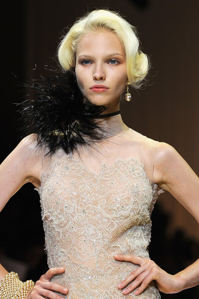 Peering down the Giorgio Armani Privé Haute Couture runway for Fall 2013, you might think you were transported by a time machine to the '20s. The hair was waved and tucked under into a classic faux bob, and the makeup appeared natural with a deep pink lipstick and a silvery shadow on lids. We wouldn't be surprised if the models hit the speakeasy soon after their catwalk debut.  The look: Faux bobs, flushed lips, and sheer metallic shadow. Who would wear it: A woman on her way to a Great Gatsby-themed party or a vintage bride. Trends: Period-inspired beauty.