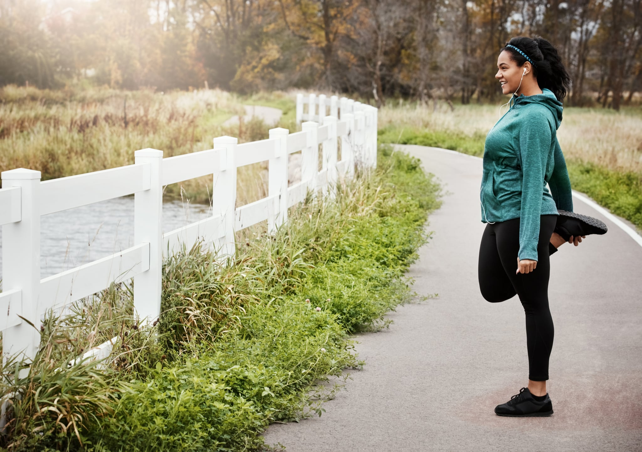 Shot of an attractive young woman stretching while out for a run in nature