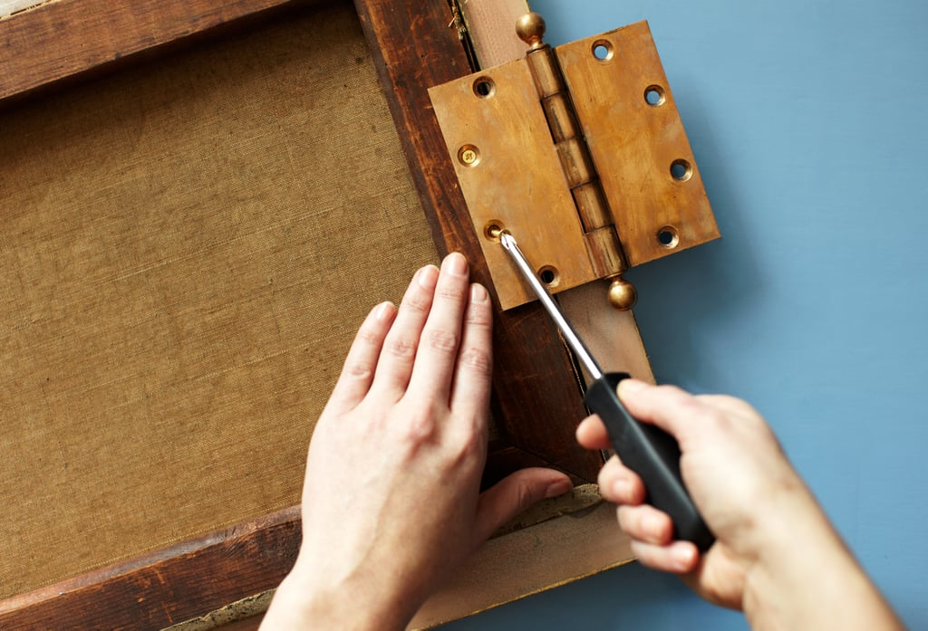 Prep the Painting  To begin, turn your painting face down on a flat, clean surface. Center your hinge along the desired side so that the middle of the hinge is aligned with the outermost edge of the painting's stretcher or frame. I prefer attaching the hinge using a screwdriver to avoid splitting the wood of the stretcher.   Note: It's important that the screws you use here are short so that they don't puncture through the painting itself.  Attach as many screws as needed. (I used only two screws because my painting was small.)