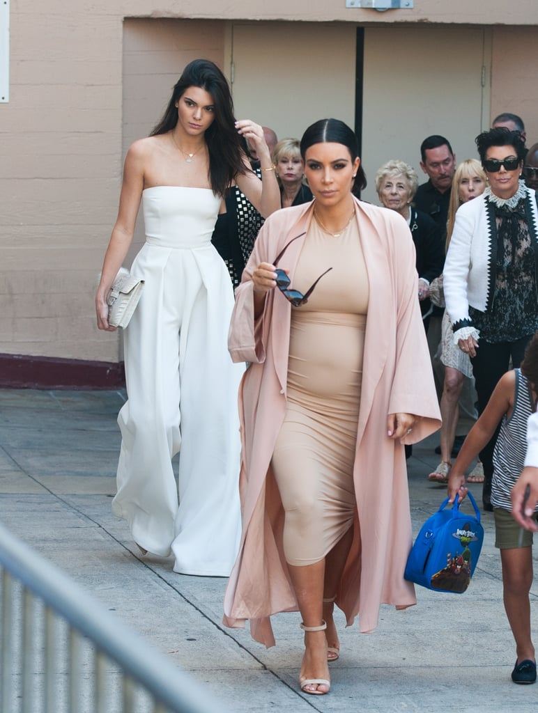 Kim chose a supertight sand-colored midi dress that matched her ankle strap sandals perfectly. She finished her outfit with a lightweight pink duster coat.