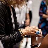 Diane tying cool ribbons of her new perfume, DIANE, around customers' wrists.