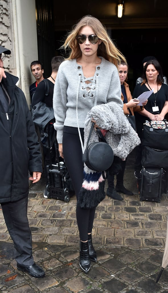 Gigi showed up to the Giambattista Valli show in a luxe-looking lace-up sweatshirt, black leggings, and her go-to pointed-toe booties. She completed her outfit with a Rag & Bone bag and oversize aviators and held onto a furry multicolor overcoat.