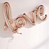 """بالون على شكل كلمة """"Love"""" بلون الذهب الورديّ (بسعر 10$ دولار أمريكيّ؛ 48 درهم إماراتيّ/ريال سعوديّ)"""