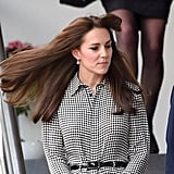 Kate's hair blew in the wind, showing off a pair of dainty pearl drop earrings.