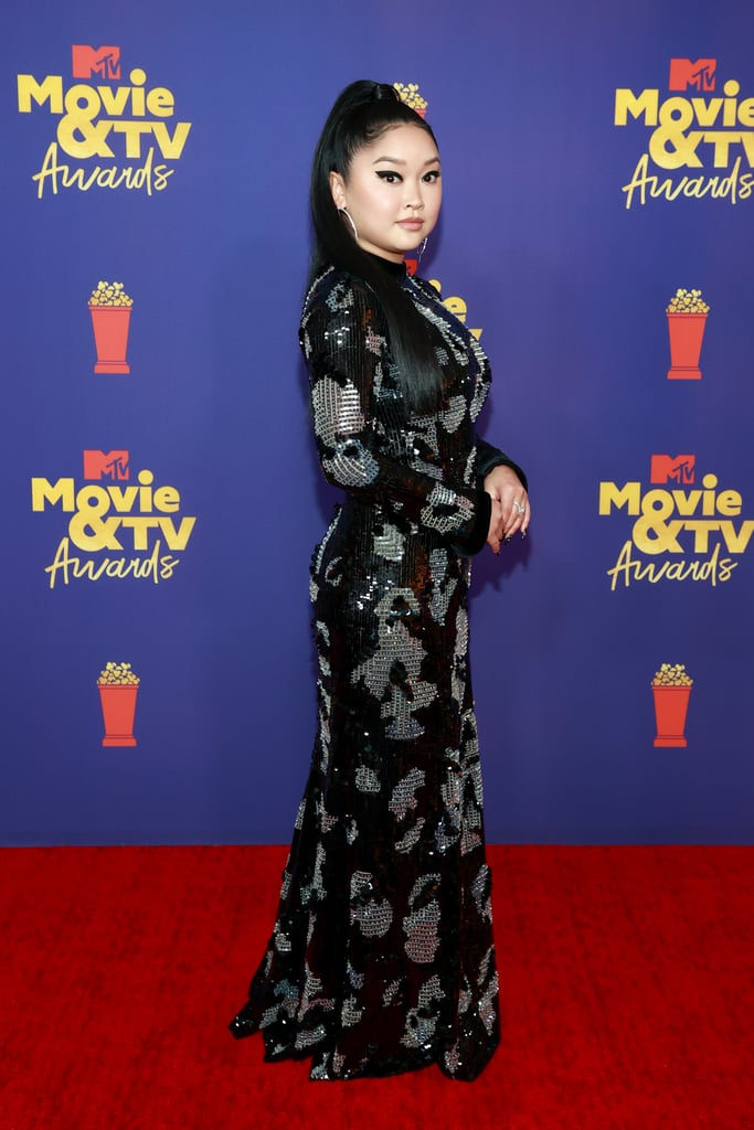 Lana Condor brought serious glam to the MTV Movie and TV Awards on Sunday night. The To All the Boys I've Loved Before actress showed up on the red carpet wearing a stunning sequinned Giorgio Armani gown that only gets more captivating the longer you look at it. She trusted longtime stylist Tara Swennen to bring this sleek look to life, pairing the turtleneck dress with statement earrings from Messika and matching nail art courtesy of Thuy Nguyen.  You'll notice every element of Lana's outfit appears meticulously planned to ensure a seamless ensemble. That's just the way she does fashion, and we love her for it. Check out more angles of Lana's look, ahead.