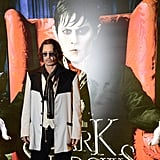 Johnny Depp posed for press in front of the Dark Shadows poster.