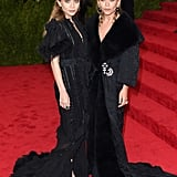 Twinning combo: M-K and A brought the drama in all black at the 2015 Met Gala.   Ashley looked glamorous in a Victorian-inspired style.  Mary-Kate pinned shimmering brooches on her luxe coatdress.