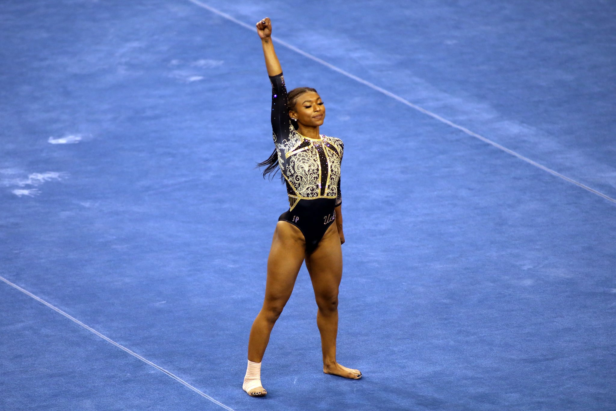 LOS ANGELES, CALIFORNIA - FEBRUARY 27: Nia Dennis of the UCLA Bruins raises a fist during her floor routine during a meet against the Oregon State Beavers at Pauley Pavilion on February 27, 2021 in Los Angeles, California. (Photo by Katharine Lotze/Getty Images)