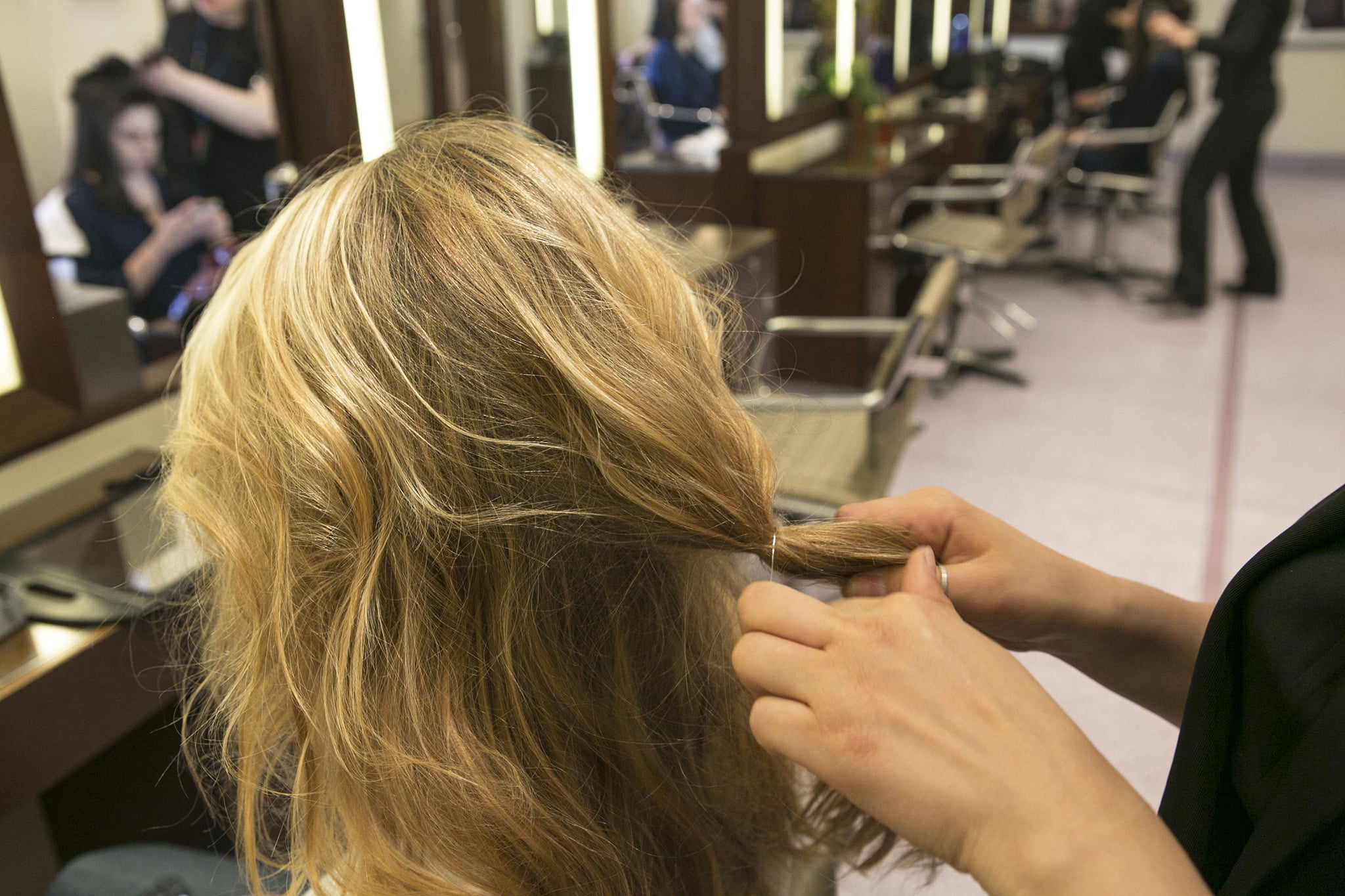 After you've teased your hair, part in the center and smooth back the middle section of hair at the crown into a loose half ponytail that's secured around the nape of the neck.