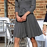 Kate wearing her gray Orla Kiely dress in 2012, accessorized with black pumps, a simple clutch, a dainty diamond bracelet, and her sapphire engagement ring.