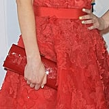 A pretty grosgrain belt cinched Zooey Deschanel's dress and she finished the look with a red clutch in hand.