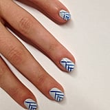 File and shape your nails to a natural square shape. Apply a base coat like JINsoon Power Coat ($18). Apply two coats of JINsoon Kookie White ($18) on the entire nail bed. With a thin brush, create thin lines using JINsoon Cool Blue ($18). Paint the first line from the top of the nail at a diagonal, ending at the opposite side of the nail. Then paint the second line perpendicular to the first line about a third of the way down the nail. Continue painting at right angles from the previous line (as shown in the photo) until you reach the end of the nail. Apply a top coat like JINsoon Top Gloss ($18) for a lasting glossy finish.