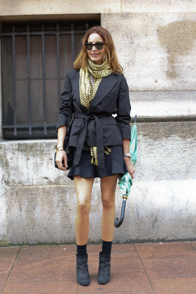 We love the way a belted blazer and booties anchor her fluted skirt.