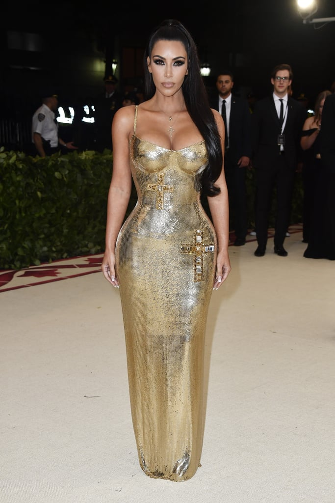 """In the wise words of Cardi B, Kim Kardashian """"came through dripping"""" at the 2018 Met Gala. On Monday, the mom of three put her captivating curves on display in a skin-tight metallic gold gown designed by Donatella Versace herself. For the """"Heavenly Bodies: Fashion and the Catholic Imagination""""-themed evening, Kim wore Lorraine Schwartz jewellery to complement the cross-emblazoned outfit that would make even Goldmember proud. While husband Kanye West was absent for the second year in a row, she illuminated the red carpet solo, leaving everyone in awe of her gold goddess ways. Read on to see the gorgeous photos of Kim at the biggest fashion event of the year.      Related:                                                                                                           Every Look at Last Year's Met Gala Was Bold Enough to Leave an Impression"""