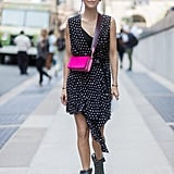 A neon bag is fun with a polka-dot dress and boots.