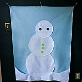 "Another toddler-appropriate game choice at this fun birthday bash was the ""Do You Want to Build a Snowman?"" felt wall arrangement game. The kids had such a splendid time giving the snowman different hats, scarves, and noses during the party."