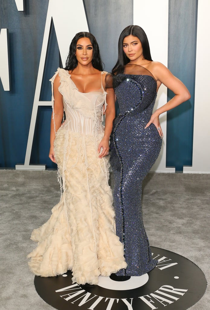 You know what we love even more than a good couple's moment? A sisters' moment! Kim Kardashian and Kylie Jenner walked into the Vanity Fair Oscars afterparty together in equally phenomenal gowns. Kim made sure to stop and take a few snaps with her husband, Kanye West, too. Kudos to Kanye for his sleek leather suit.  Kim kept to her signature neutrals in a beige textured gown, while Kylie went for sparkles in a navy dress. The outfits perfectly complemented each other and looked fabulous flowing down the gray carpet. Make sure to check out all the family photos the crew took before heading into the party.