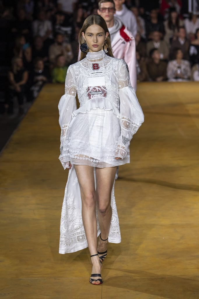 "Riccardo Tisci continued to put his own unique spin on Burberry during the Spring 2020 show, but this time around, in contrast to last season's '90s rave-inspired collection, the show had a more airy feel, and even a touch of Victorian romance. The show was titled ""Evolution"" and did indeed seem to represent the designer finding his footing when it comes to managing the expectations of the heritage consumer with his own modern approach to fashion. Beige separates with all the classic Burberry trademarks opened the show (those ubiquitous trench coats, midi skirts, and shirts with logo-emblazoned collars) before segueing into a sequence of more experimental styles, tinged with aviation-inspired touches like clip fastening, bodysuits with the poppers left open, and parachute coats, almost exclusively in cream, black, and white, dotted with the occasional red gingham. They were topped with baseball caps with bonnet-like brims, or even, in one case, a crystal-studded veil. For Tisci's fans who prefer a more glamorous look (Kim Kardashian, we're looking at you), there were crystal-encrusted suits, sparkling sheer dresses with visible labels on the chest (a knowing nod to the logomania trend), and lacy, Victorian confections that matched the men's basketball shorts with lacy trims. The finale dresses, dusted with ostrich feathers, offered a final dose of red carpet glamour. See it all for yourself ahead."