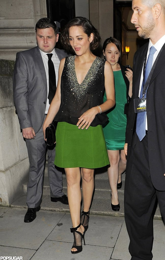 Marion Cotillard matched a loose black top with a green skirt.