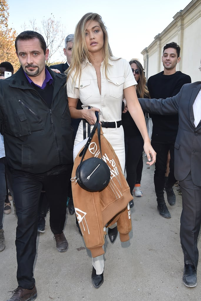 Gigi showed up to the Elie Saab show in a cream, '70s-inspired dungaree jumpsuit, which she completed with a black belt, booties, and a Rag & Bone crossbody bag.