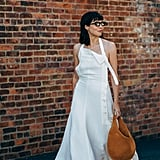 Kat Collings knows that a simple mesh kitten-heel mule and oversize hobo bag elevate a basic white maxi.