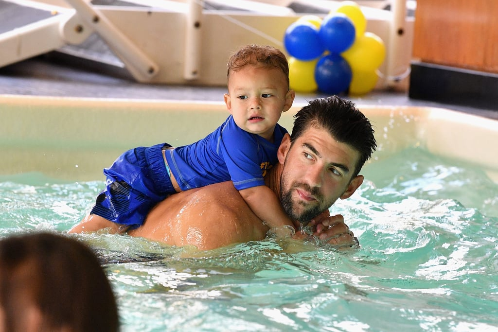 "Michael Phelps is passing on his incredible talents in a big way. On Monday, the Olympic gold medalist hosted the Huggies Little Swimmers Swim Class on behalf of his Phelps Foundation and was naturally joined by his wife, Nicole Johnson, and their 1-year-old son, Boomer. The trio waded in the pool with a handful of other parents and babies, and the cameras caught some truly precious moments between Michael and his little boy, who rode on his dad's shoulders through the water.   In an interview with POPSUGAR in June, Michael said of Boomer, ""I like to be able to chill with him and just relax,"" and when asked about the potential of Boomer becoming an athlete, he replied, ""I went through ups and downs in the pool when I loved it and when I hated it, so if he wants to be an athlete of some sort, great. If he doesn't, OK,"" adding, ""The more you push a kid, in my opinion, they go the other direction, so I won't push him to do that."" Judging by these photos, it looks like Boomer is totally fine with cruising on his dad's back for now.      Related:                                                                                                           15 Reasons It Should Be Illegal For Michael Phelps to Wear a Shirt"