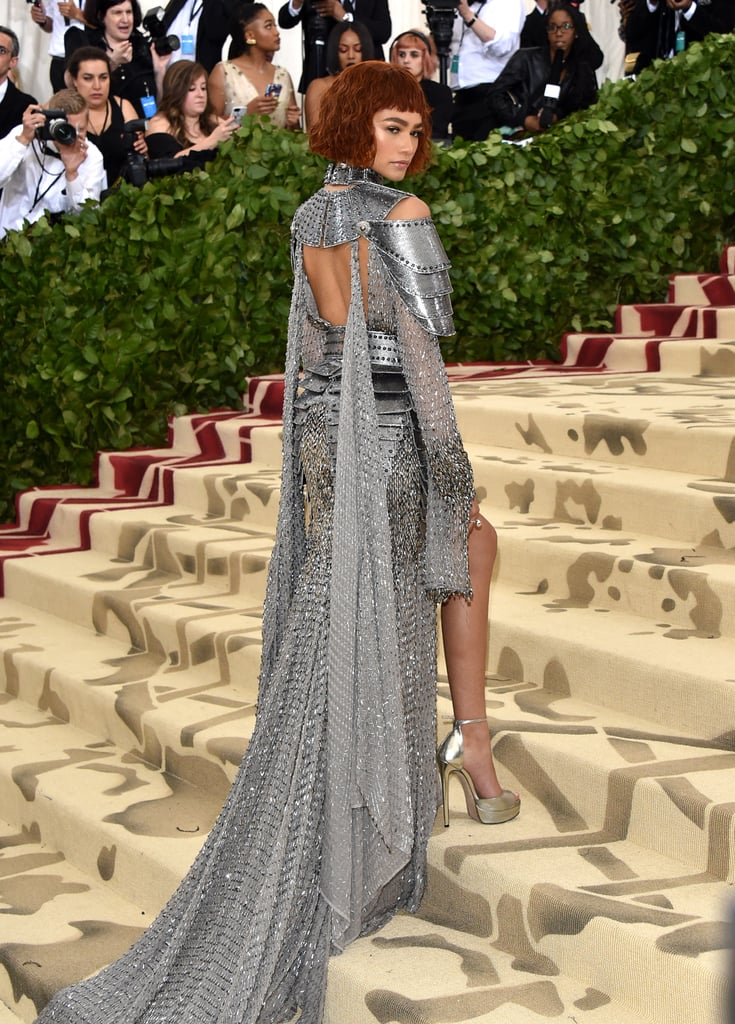 Is that Joan of Arc or Zendaya? It's Zendaya paying homage to the fearless crusader at the Met Gala. The 21-year-old actress and singer arrived in a spectacular silver Versace dress that literally looked like a knight's armor with the metal shoulder pads and chain details. She paired it with matching Jimmy Choo heels and Tiffany & Co. jewelry. When she turned around, you could see the back peephole and her gorgeous chain-link train, which looked heavy to haul up those steps.  This dress is astoundingly similar to the paintings that exist of Joan of Arc. Zendaya even channeled the saint with her red hair and simple makeup look. Keep scrolling to take all in of Zendaya's angles and be in awe of her overall look.