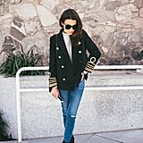 A double-breasted blazer layered over a mock neck sweater, jeans, and ankle boots.