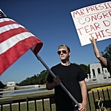 "At DC's WWII Memorial, protestors held up a flag and a sign that read, ""Mr. President, Congress, Tear down this wall!"""