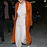 Kendall Walked Through the Airport on Wednesday Wearing an Orange Duster Over Her Beige Outfit