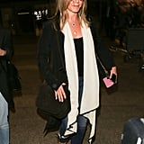 Jennifer catching a flight in LAX wearing a black tank top, jeans, and a white scarf in July 2016.