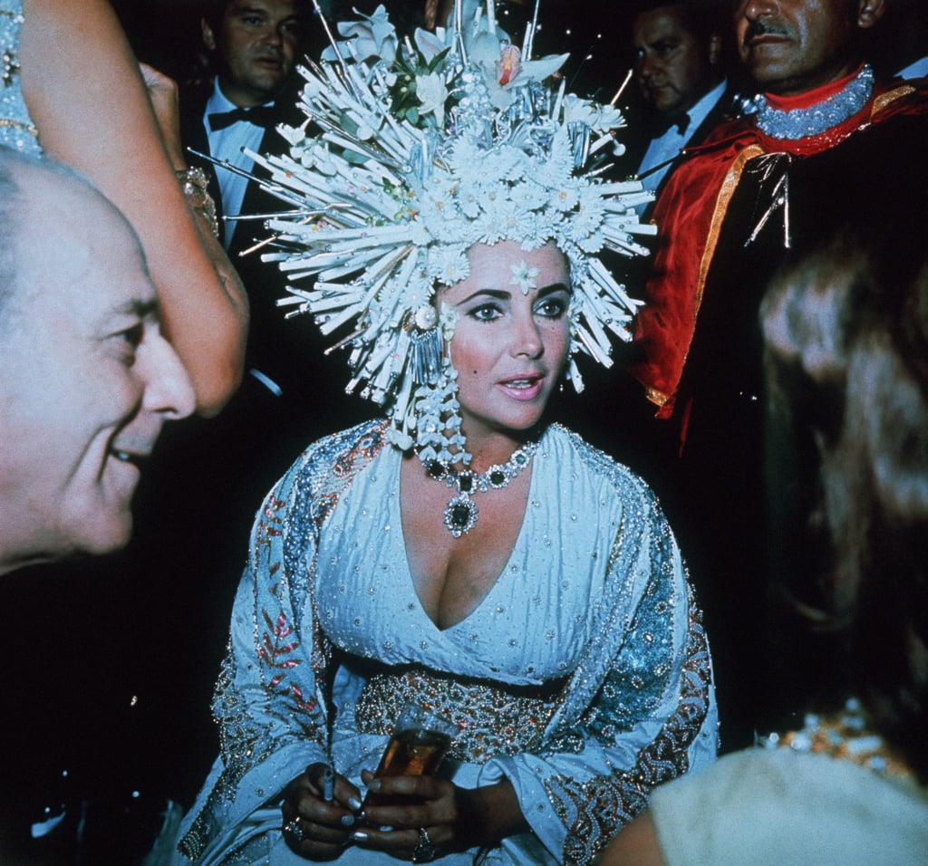 It's been six years since Elizabeth Taylor passed away, and the Hollywood legend left behind a legacy of classic films, HIV/AIDS activism, and iconic style. Elizabeth found a way to make the trends of each decade work for her, whether it was the form-fitting dresses of the 1950s, the floaty caftans of the '60s and '70s, or the shoulder pads and bold prints of the '80s — but one major style staple that Elizabeth owned more than any other was her headwear. Liz had some of the strongest hat game in Hollywood, from oversize headdresses to bright, artfully wrapped scarves. While she certainly didn't begin the headwrap craze, Elizabeth Taylor definitely made it one of her signatures. Read on for the legendary actress's most stylish headwear moments.      Related:                                                                                                           From Bold to Beautiful to Downright Ridiculous, Here Are the Best Hats Worn by the Royal Family