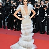 For a glamorous night on the Cannes Film Festival red carpet, Kendall wowed in a super-sheer gown by Schiaparelli that featured a plunging neckline with a tiered skirt and ruffled shoulders. The model accessorized her gown with a matching belt, a diamond seahorse pin, and a pair of Chopard statement earrings.