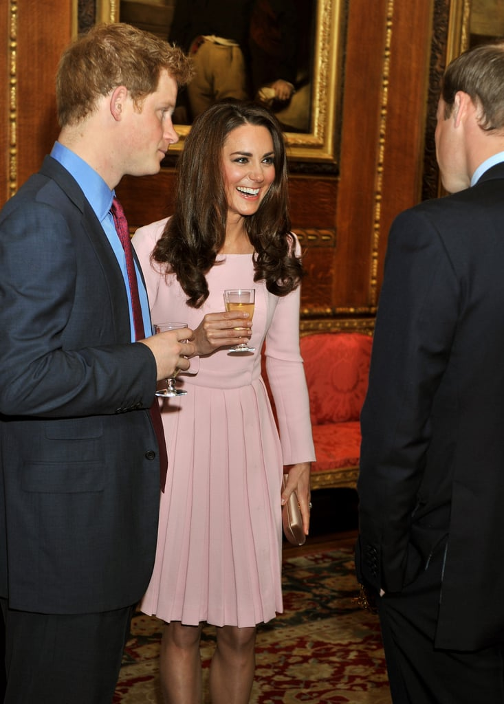 Kate Middleton, the Duchess of Cambridge, was the lucky lady hanging out with both her husband, Prince William, and his little brother, Prince Harry, today! The trio attended a reception in London's Waterloo Chamber ahead of a lunch for visiting monarchs at Windsor Castle. Kate Middleton wore a dress from Emilia Wickstead, a pale pink coat-style frock that costs nearly $2,000.  At the meal, Harry, William, Kate, and Queen Elizabeth mingled with kings, queens, and heads of state from 26 countries. William and Harry's cousins, Princesses Beatrice and Eugenie, were also on hand to chat with dignitaries like Monaco's Prince Albert and Princess Charlene and Jordan's King Abdullah and Queen Rania. There may be protests in England this evening, though, as some aren't thrilled the royals included the King of Bahrain, who's accused of committing human rights abuses during a recent period of unrest in his country. British fare was served to Kate, William, their family, and guests, starting with a poached egg tartlet and then a main of Windsor lamb. This evening, William's father Prince Charles is hosting a dinner reception with his wife Camilla, Duchess of Cornwall.