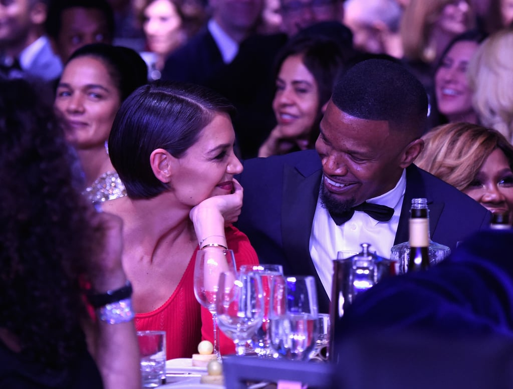 """Jamie Foxx and Katie Holmes are coming out of hiding. The notoriously private couple made a rare appearance together at Clive Davis's annual pre-Grammys bash in NYC on Saturday night. Clive reportedly """"gave them a hard time"""" from the stage when Jamie and Katie opted not to sit next to each other at first. Later, they switched seats and were spotted side by side staring lovingly at one another, Katie whispering into Jamie's ear. The pair, who were first linked back in 2013, were all smiles throughout the evening. This marks their first official outing after the two were photographed holding hands on the beach in September. Katie also popped up at Jamie's 50th birthday bash and supported him at his Prive Revaux eyewear store opening in December. Read on to see more photos from Jamie and Katie's sweet night out."""