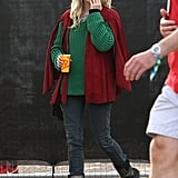 Sienna Miller simultaneously kept warm and cool in a red cape, a green sweater, and studded boots.