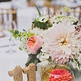Add glitter to a votive holder with a flower for festive table decorations.