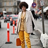 Et voilà! Suit separates become a multidimensional, contemporary look with an overcoat slung nonchalantly over the shoulders.